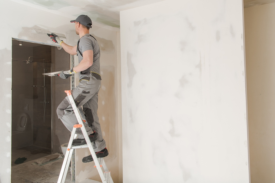 man putting putty on the corner of the wall