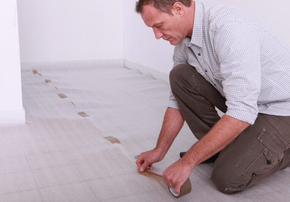 man taping the sheet on the flooring